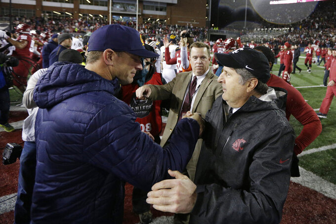 California head coach Justin Wilcox, left, and Washington State head coach Mike Leach speak after an NCAA college football game in Pullman, Wash., Saturday, Nov. 3, 2018. Washington State won 19-13. (AP Photo/Young Kwak)
