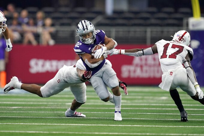 Kansas State running back Deuce Vaughn (22) carries the ball as Stanford linebacker Jordan Fox , rear, and cornerback Kyu Blu Kelly (17) attempt to make a stop in the second half of an NCAA college football game in Arlington, Texas, Saturday, Sept. 4, 2021. (AP Photo/Tony Gutierrez)
