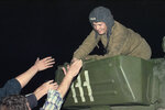 FILE - In this Monday, Aug. 19, 1991 file photo, Muscovites reach up to shake the hand of a soldier atop a tank near the Russian parliament building in Moscow, Russia. When I reached the headquarters of Yeltsin's government, I saw crowds of people swarming tanks sent to encircle the building. Some of the crews got out of their vehicles and declared that they would side with protesters. (AP Photo/Alexander Zemlianichenko, File)