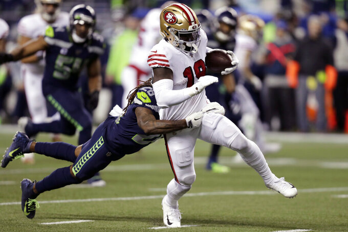 San Francisco 49ers' Deebo Samuel (19) carries the ball as Seattle Seahawks' Shaquill Griffin tries to pull him down during the second half of an NFL football game, Sunday, Dec. 29, 2019, in Seattle. (AP Photo/Stephen Brashear)