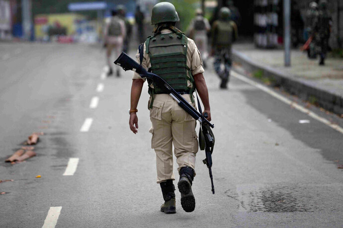 FILE- In this Aug. 15, 2019 file photo, Indian paramilitary soldiers patrol in Srinagar, Indian controlled Kashmir. Police in Indian-controlled Kashmir have arrested a long-serving counterinsurgency officer for allegedly having ties with rebels fighting against Indian rule in the disputed region, officials said Sunday. (AP Photo/ Dar Yasin, File)