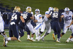 BYU quarterback Zach Wilson, center, looks to throw downfield as Navy defensive tackles Jackson Perkins (96) and Deondrae Williams (92) apply pressure during the first half of an NCAA college football game, Monday, Sept. 7, 2020, in Annapolis, Md. (AP Photo/Tommy Gilligan)