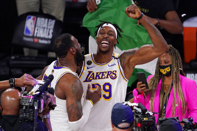 Los Angeles Lakers' LeBron James (23) and Los Angeles Lakers' Dwight Howard (39) celebrate after the Lakers defeated the Miami Heat 103-88 in Game 6 of basketball's NBA Finals Sunday, Oct. 11, 2020, in Lake Buena Vista, Fla. (AP Photo/Mark J. Terrill)