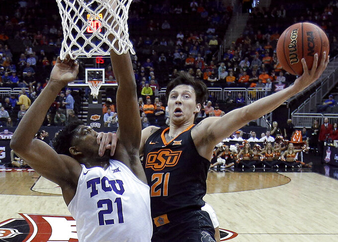 Oklahoma State's Lindy Waters III, right, puts up a shot under pressure from TCU's Kevin Samuel during the first half of an NCAA college basketball game in the Big 12 men's tournament Wednesday, March 13, 2019, in Kansas City, Mo. (AP Photo/Charlie Riedel)