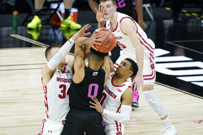 Penn State's Myreon Jones (0) is trapped by Wisconsin's Brad Davison (34) and D'Mitrik Trice (0) during the second half of an NCAA college basketball game at the Big Ten Conference tournament, Thursday, March 11, 2021, in Indianapolis. (AP Photo/Darron Cummings)