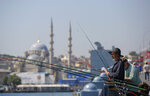 People fish on Galata Bridge with Yeni Cami in the background in Eminonu district in Istanbul, Tuesday, July 27, 2021. Turkey has recorded more than 15,000 new coronavirus cases, as the number of infections continue to surge. (AP Photo/Mucahid Yapici)