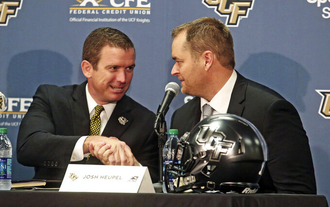 """FILE - In this Dec. 5, 2017, file photo, Josh Heupel, right, is introduced as the new Central Florida head football coach by Danny White, UCF Athletic director in Orlando, Fla. Southeastern Conference Commissioner Greg Sankey says UCF should look """"inward"""" to address strength of schedule issues that have held back the Knights in the College Football Playoff rankings. White says Knights can do nothing to fix an """"inadequate postseason."""" (Red Huber/Orlando Sentinel via AP, File)"""