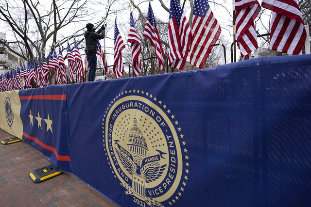 A worker installs flags on Pennsylvania Avenue in front of the White House ahead of President-elect Joe Biden's inauguration ceremony, Tuesday, Jan. 19, 2021, in Washington. (AP Photo/David Phillip)