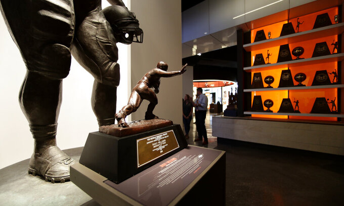 Visitors walk through the Frank Denius Family University of Texas Athletics Hall of Fame, Friday, Aug. 30, 2019, in Austin, Texas. Displays honor all 55 of Texas' National Championship teams, 599 conference team titles, hundreds of individual national champions, 171 Olympians at 21 Olympiads, academic All-Americans and other scholastic honorees, as well as the traditions and tales that encompass the history of Longhorns. (AP Photo/Eric Gay)