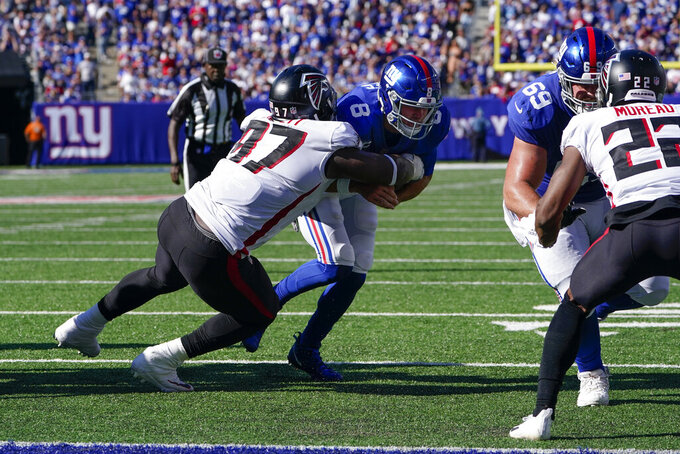 New York Giants quarterback Daniel Jones (8) runs the ball against Atlanta Falcons defensive tackle Grady Jarrett (97) for a two-point conversion during the second half of an NFL football game, Sunday, Sept. 26, 2021, in East Rutherford, N.J. (AP Photo/Seth Wenig)