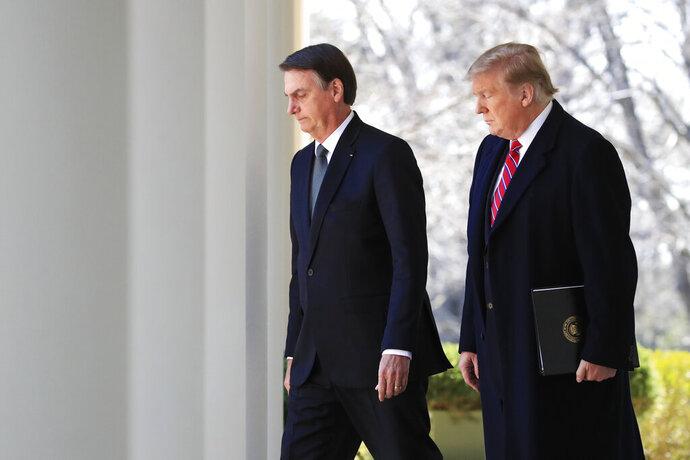 President Donald Trump and visiting Brazilian President Jair Bolsonaro walk along the Colonnade of the White House, March 19, 2019, in Washington. (AP Photo/Manuel Balce Ceneta)