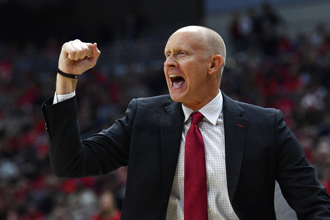 "FILE - In this Dec. 6, 2019, file photo, Louisville head coach Chris Mack reacts to a play during the first half of an NCAA college basketball game in Louisville, Ky. Louisville has received a notice of allegations from the NCAA, Monday, May 4, 2020, that accuses the men's basketball program of committing a Level I violation with an improper recruiting offer and extra benefits and several Level II violations that accuse former Cardinals coach Rick Pitino of failing to promote an atmosphere of compliance. ""While I understand the allegations brought today, I am confident that the University will do what is right, which includes fighting back on those charges that we simply do not agree with, and for which the facts do not substantiate,"" Mack said in a statement. (AP Photo/Timothy D. Easley, File)"