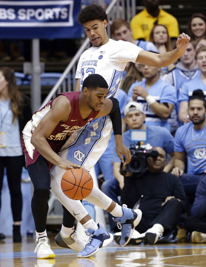 North Carolina's Cameron Johnson, top, guards against Florida State's M.J. Walker during the first half of an NCAA college basketball game in Chapel Hill, N.C., Saturday, Feb. 23, 2019. (AP Photo/Gerry Broome)