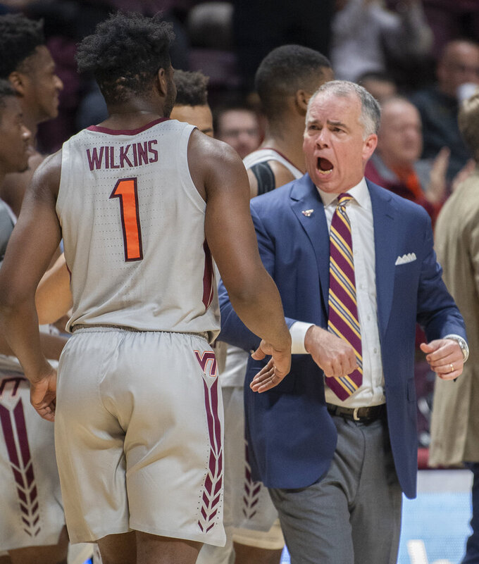 Virginia Tech head coach Mike Young encourages his player, Virginia Tech guard Isaiah Wilkins (1) during the first half of an NCAA college basketball game Sunday, Dec. 15, 2019 in Blacksburg, Va. (Don Petersen/Roanoke Times via AP)
