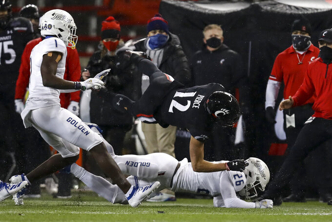 Cincinnati wide receiver Alec Pierce (12) is tackled by Tulsa cornerback Akayleb Evans (26) during the first half of the American Athletic Conference championship NCAA college football game, Saturday, Dec. 19, 2020, in Cincinnati. (AP Photo/Aaron Doster)