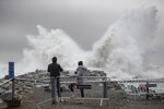 Two people watch the waves hitting the breakwater in Barcelona, Spain, Wednesday, Jan. 22, 2020. Massive waves and gale-force winds smashed into seafront towns, damaging many shops and restaurants and flooding some streets. (AP Photo/Joan Mateu)