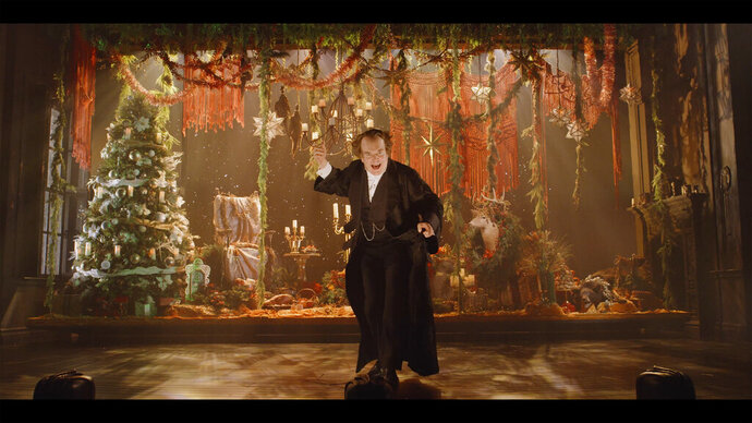 """Tony Award-winner Jefferson Mays performs during a one-man high-tech """"A Christmas Carol Live"""" that is being filmed for streaming this month at the empty 3,000-seat United Palace. The one-man show is an example of how many who work in the theater are increasingly defying COVID-19 by refusing to let it stop their art. (Courtesy of A Christmas Carol Live via AP)"""