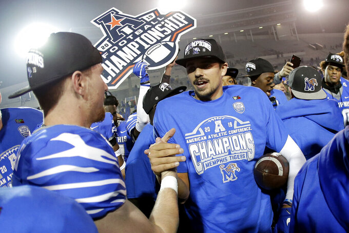 FILE - In this Dec. 7, 2019, file photo, Memphis quarterback Brady White, center, celebrates after his team defeated Cincinnati in an NCAA college football game for the American Athletic Conference championship, in Memphis, Tenn. The American Athletic Conference will require all its schools to test football players for COVID-19 at least 72 hours before competition. The announcement Thursday, July 16, 2020, by the American comes ahead of the expected release of recommendations for testing before games from the NCAA. (AP Photo/Mark Humphrey, File)