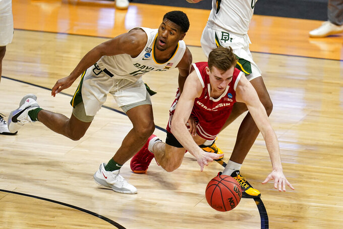 Wisconsin forward Tyler Wahl (5) dives in front of Baylor guard Jared Butler (12) for a loose ball in the first half of a second-round game in the NCAA men's college basketball tournament at Hinkle Fieldhouse in Indianapolis, Sunday, March 21, 2021. (AP Photo/Michael Conroy)