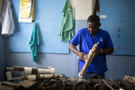 In this June 4, 2019 photo, prosthetic technician Wilfrid Macena works in a workshop at the St. Vincent's Center, an institution run by Haiti's Episcopal Church in downtown Port-au-Prince, where a small group of disabled workers fit those who have lost limbs with prosthetics. (AP Photo/Dieu Nalio Chery)