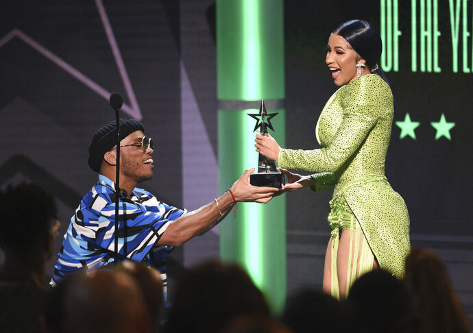 Anderson .Paak, left, presents the album of the year award to Cardi B at the BET Awards on Sunday, June 23, 2019, at the Microsoft Theater in Los Angeles. (Photo by Chris Pizzello/Invision/AP)
