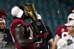 Alabama offensive lineman Alex Leatherwood kisses the the trophy after their win against Ohio State in an NCAA College Football Playoff national championship game, Tuesday, Jan. 12, 2021, in Miami Gardens, Fla. Alabama won 52-24. (AP Photo/Chris O'Meara)