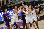 Texas Tech forward Marcus Santos-Silva (14) and guard Mac McClung vie with Northwestern State forward Jamaure Gregg for a rebound during the first half of an NCAA college basketball game Wednesday, Nov. 25, 2020, in Lubbock, Texas. (AP Photo/Mark Rogers)