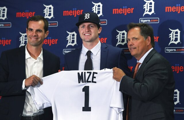 FILE - In this June 25, 2018, file photo, Detroit Tigers first overall pick Casey Mize, center, stands with Tigers scout Justin Henry, left, and Scott Pleis, director of amateur scouting, during a news conference where he was introduced to the media, in Detroit. Mize was the No. 1 pick in the 2018 draft. He's one of two pitchers headlining Detroit's rebuilding process. The Tigers held their first workout for pitchers and catchers Wednesday, Feb. 12, 2020 and while only the most optimistic Detroit fan would predict a great season in 2020, there are finally some signs of promise. (AP Photo/Carlos Osorio, File)