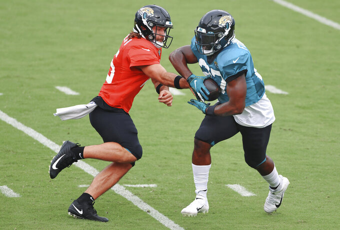 Jacksonville Jaguars starting quarterback Gardner Minshew II, left, hands the ball off to running back Leonard Fournette during NFL football training camp, Saturday, Aug. 29, 2020, in Jacksonville, Fla. (Bob Self/The Florida Times-Union via AP)
