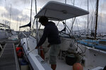 A man places boat fenders alongside his boat at the Horta Marina in preparation for the arrival of hurricane Lorenzo in Horta, the capital of the Portuguese island of Faial, Tuesday, Oct. 1, 2019. The Category 2 hurricane is expected to hit the Atlantic Ocean Portuguese archipelago of the Azores Tuesday night and Wednesday morning. Lorenzo was previously a Category 5 hurricane, the strongest storm ever observed so far north and east in the Atlantic basin. (AP Photo/Joao Henriques)