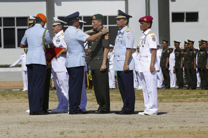 In this May 11, 2018, photo, Indonesia Armed Forces Chief Air Marshall Hadi Tjahjanto, second left, puts on an epaulet on the shoulders of a military general during their inauguration to their new position in Sorong, Papua province, Indonesia. The Indonesian government is planning to post some of the dozens of underemployed generals into high-ranking civilian roles, alarming rights groups who see it as a threat to the country's young democracy. (AP Photo/Tatan Syuflana)