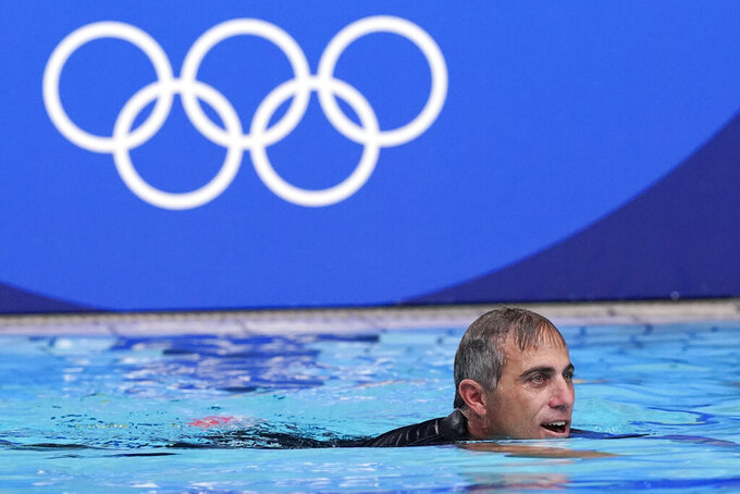 United States head coach Adam Krikorian swims in the pool following his team's win over Spain in the women's water polo gold medal match at the 2020 Summer Olympics, Saturday, Aug. 7, 2021, in Tokyo, Japan. (AP Photo/Mark Humphrey)