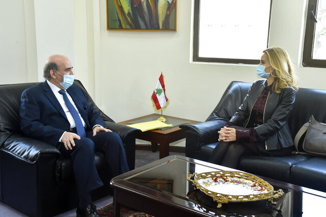 In this photo released by Lebanon's official government photographer Dalati Nohra, Lebanese Foreign Minister Charbel Wehbi, left, meets with Switzerland's ambassador to Lebanon Monika Schmutz Kirgöz, right, in Beirut, Lebanon, Monday, Jan. 25, 2021. Wehbi held talks Monday with Kirgöz days after Switzerland started a probe into possible money laundering and embezzlement at the country's central bank. (Dalati Nohra via AP)