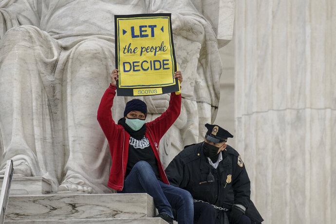A protester opposed to the Senate's race to confirm Amy Coney Barrett is removed by police after chaining themselves to a railing and holding a sign while sitting atop the statue Contemplation of Justice, at the Supreme Court building in Washington, Sunday, Oct. 25, 2020. (AP Photo/J. Scott Applewhite)