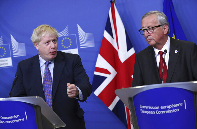 British Prime Minister Boris Johnson and European Commission President Jean-Claude Juncker make prepared statements during a press point at EU headquarters in Brussels, Thursday, Oct. 17, 2019. Britain and the European Union reached a new tentative Brexit deal on Thursday, hoping to finally escape the acrimony, divisions and frustration of their three-year divorce battle. (AP Photo/Francisco Seco)