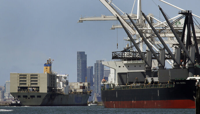 FILE - In this May 17, 2019, file photo, a tugboat assists as a container ship is prepared for docking at the Port of Oakland in Oakland, Calif. The president of the Oakland City Council in the San Francisco Bay Area is proposing bringing a cruise ship to the city's port to house up to 1,000 homeless people. (AP Photo/Ben Margot,File)