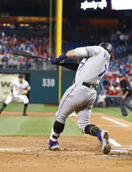 Colorado Rockies' Brendan Rodgers hits a ground ball that drove in a run during the second inning of the team's baseball game against the Philadelphia Phillies, Friday, May 17, 2019, in Philadelphia. Rodgers reached on the fielder's choice. (AP Photo/Chris Szagola)
