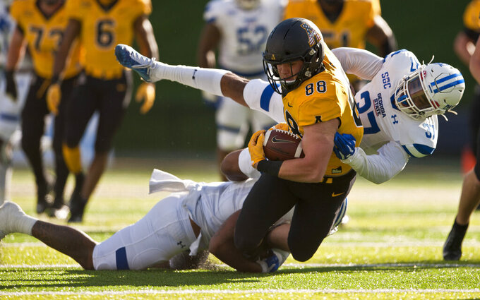 Appalachian State tight end Henry Pearson is taken down by Georgia State's Trajan Stephens-McQueen (6) and Victor Heyward (37) after a first-half reception during an NCAA football game, Saturday, Nov. 14, 2020, in Boone, N.C. (Walt Unks/Winston-Salem Journal via AP)