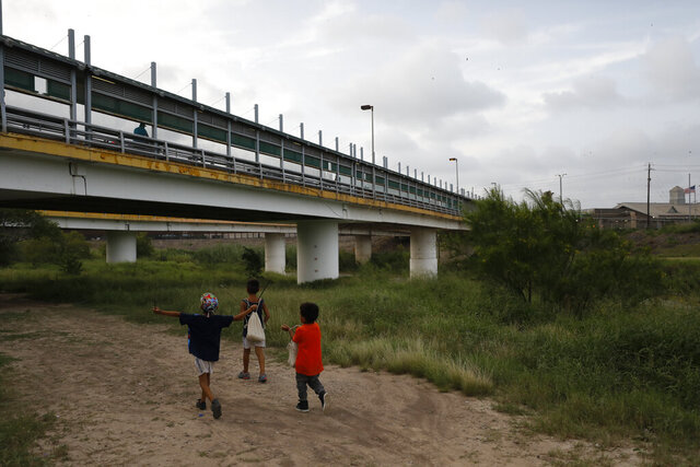 FILE - In this June 26, 2019 file photo, migrant children walk with their families along the Rio Grande, as pedestrian commuters use the Puerta Mexico bridge to enter Brownsville, Texas, seen from Matamoros, Tamaulipas state, Mexico. The U.S. this week started having immigrant children held in Houston appear before a judge based in Atlanta, in what advocates say is a pilot that could portend a nationwide expansion of video hearings for kids. While the government would not confirm its plans, advocates warned of a greater burden being placed on detained immigrant children, many of whom are not yet teenagers and don't have guaranteed access to an attorney.  (AP Photo/Rebecca Blackwell, File)