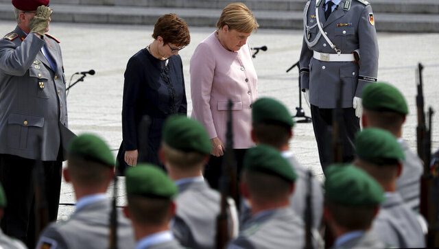 "FILE -- In this Saturday, July 20, 2019 file photo German Chancellor Angela Merkel, center right, and German Defence Minister Annegret Kramp-Karrenbauer, center left, bow in front of soldiers during an oath-taking ceremony of the German army at the Defence Ministry in Berlin, Germany. Germany's defense minister is apologizing for decades of discrimination against gay servicepeople in the military until a change of policy in 2000. A study commissioned by the defense ministry and being presented Thursday documented ""systematic discrimination"" from 1955 until the end of the 20th century. (AP Photo/Michael Sohn)"