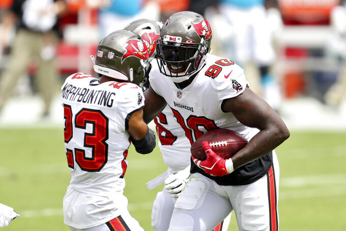 Tampa Bay Buccaneers defensive end Jason Pierre-Paul (90) celebrates with cornerback Sean Murphy-Bunting (23) after Pierre-Paul recovered a fumble by Carolina Panthers quarterback Teddy Bridgewater during the first half of an NFL football game Sunday, Sept. 20, 2020, in Tampa, Fla. (AP Photo/Mark LoMoglio)