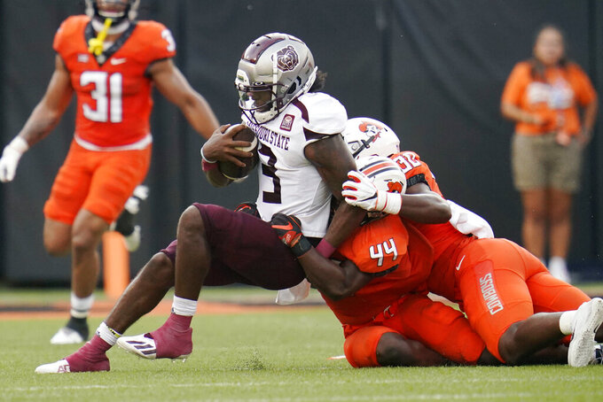 Missouri State quarterback Jason Shelley (3) is tackled by Oklahoma State linebacker Kamryn Farrar (44) and defensive end Collin Oliver (30) in the first half of an NCAA college football game, Saturday, Sept. 4, 2021, in Stillwater, Okla. (AP Photo/Sue Ogrocki)