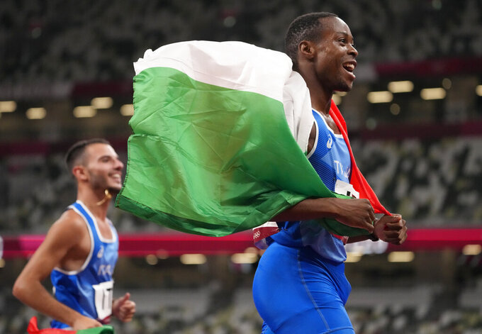 Lorenzo Patta and Eseosa Desalu, right, of Italy celebrate after taking the gold medal in the final of the men's 4 x 100-meter relay at the 2020 Summer Olympics, Friday, Aug. 6, 2021, in Tokyo, Japan. (AP Photo/Charlie Riedel)