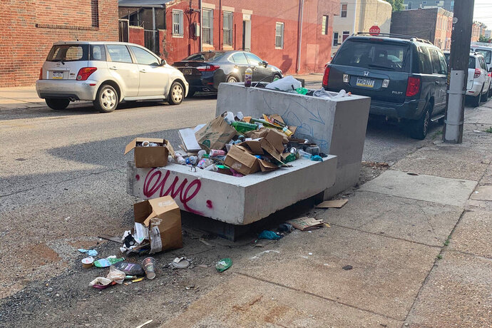 Trash rests piled up on a street Monday, July 27, 2020, in Philadelphia. The COVID-19 pandemic has frustrated efforts to keep Philadelphia's streets clear of garbage this summer. People are staying home and generating more garbage, but the sanitation department has been shorthanded and workers have fallen behind picking up household trash and recyclables. Residents complain about the stink and the flies. (Kara Kneidl via AP)