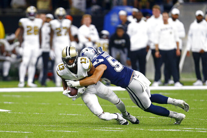 New Orleans Saints wide receiver Michael Thomas (13) is brough down by Dallas Cowboys outside linebacker Leighton Vander Esch on a pass play in the first half of an NFL football game in New Orleans, Sunday, Sept. 29, 2019. (AP Photo/Butch Dill)