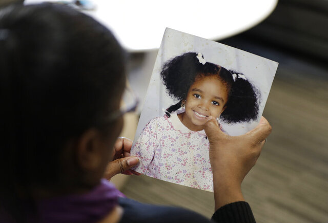 In this Oct. 29, 2019, photo, Donnesha Cooper touches a photo of her daughter, Alianna DeFreeze, in Cleveland. Her daughter's murder and the murder of Reagan Tokes had a lot in common. Yet only one victim got a law with her name on it, Tokes, who was white. An Associated Press analysis found that more than 8 in 10 stand-alone laws named for victims of violent crime identified since 1990 honored white victims or groups of victims that included at least one white person. That has left black victims such as DeFreeze underrepresented by such laws. (AP Photo/Tony Dejak)