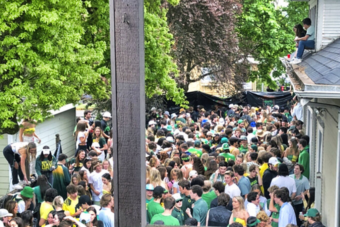 """In this May 1, 2021 photo provided by Mojo Hill,  University of Oregon students and fans gathering at a cramped outdoor party in Eugene, Ore. The University of Oregon says it is """"disappointed"""" to see the photo of more than 100 students at the same time that the region weathers a spike in cases of COVID-19 and businesses endure new restrictions. None of the packed party-goers in the photo are wearing masks. Eugene police responded to the party Saturday after calls about the large crowd, loud music and about people urinating in the front yard. (Mojo Hill via AP)"""