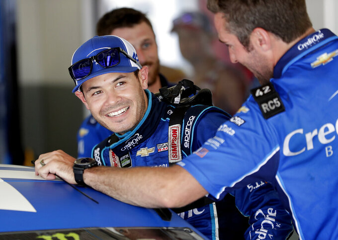 FILE - In this July 5, 2018, file photo, Kyle Larson laughs with crew members as he gets ready for NASCAR auto racing practice at Daytona International Speedway in Daytona Beach, Fla. As Larsen enters his sixth season at NASCAR's top level it is clear that once he starts winning on a consistent basis he could become the biggest star in the country. (AP Photo/John Raoux, File)
