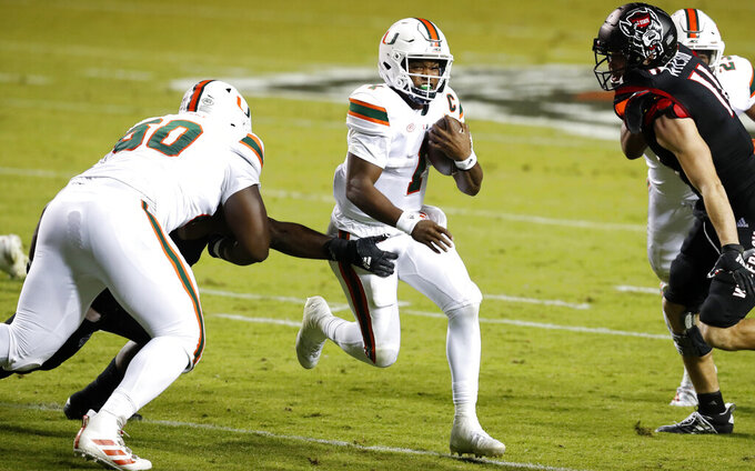 FILE - In this Nov. 6, 2020, file photo, Miami quarterback D'Eriq King (1) runs past North Carolina State linebacker Isaiah Moore, obscured at left, during the first half of an NCAA college football game in Raleigh, N.C. King and the Hurricanes visit Duke on Saturday night in their first game since Nov. 14. (Ethan Hyman/The News & Observer via AP, Pool)