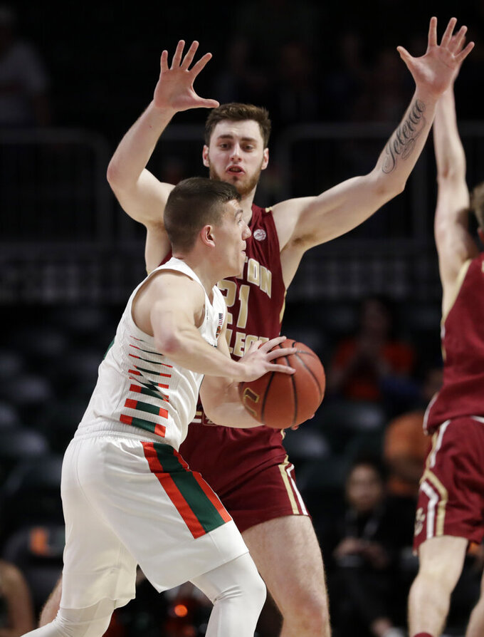 Miami guard Dejan Vasiljevic, left, looks to pass as Boston College forward Nik Popovic defends during the first half of an NCAA college basketball game, Wednesday, Feb. 12, 2020, in Coral Gables, Fla. (AP Photo/Lynne Sladky)